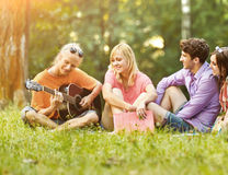 A group of students with a guitar resting in the Park Stock Photo
