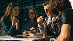 Group of Students Have Conversation. Working process in group of students, study discussion outdoors on table with laptop and books before modern building, sunny stock footage