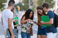 A group of students having fun with smartphones after class Foto de Stock Royalty Free