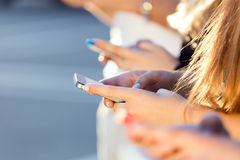 A group of students having fun with smartphones after class. Royalty Free Stock Images