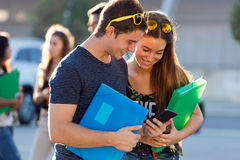 A group of students having fun with smartphones after class. Royalty Free Stock Photo