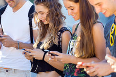 A group of students having fun with smartphones after class. Royalty Free Stock Photos