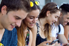 A group of students having fun with smartphones after class. Stock Photography