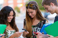 A group of students having fun with smartphones after class. Royalty Free Stock Photography