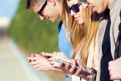 A group of students having fun with smartphones after class. Stock Images