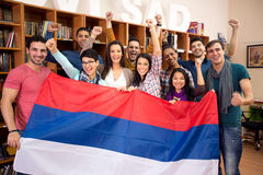 Group of students hold Serbian flag and raised victory fists Stock Photo