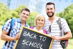 Group of students holding a back to school blackboard in the par Royalty Free Stock Photo