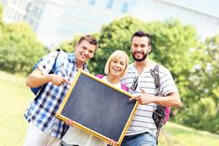 Group of students holding a blackboard in the park Royalty Free Stock Photo
