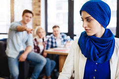 Group of students humiliating young muslim woman. My belief. Pleasant cheerless muslim women sittign in the cafe while other people humiliating her royalty free stock photography