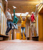 Group of students jumping in college corridor Stock Photo