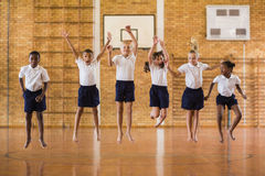 Group of students jumping in school gym Royalty Free Stock Images