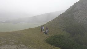 Group of students on leisure trip enjoying while hiking in the mountain admiring the nature and relaxing on grass - stock footage