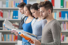 Group of students in the library. Group of college students in the library standing in line, holding books and reading, bookshelves on background Royalty Free Stock Photography