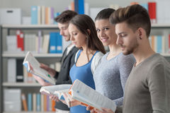 Group of students in the library. Group of college students in the library standing in line, holding books and reading, one is smiling at camera Stock Photography