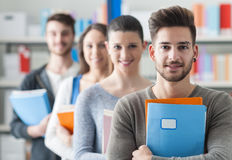Group of students in the library. Group of college students in the library standing in line and looking at camera, knowledge and studying concept Royalty Free Stock Photo