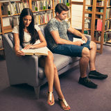 Group of students in library reading books - study group. Two students sitting on sofa in library reading books - study group Royalty Free Stock Images
