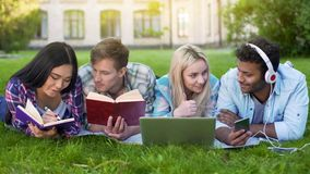 Group of students lying on grass, preparing for final exam, university education. Stock photo stock photo