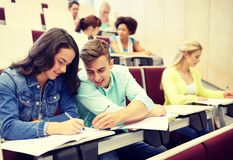 Group of students with notebooks at lecture hall royalty free stock photo