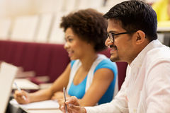 Group of students with notebooks in lecture hall Royalty Free Stock Photo