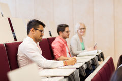 Group of students with notebooks in lecture hall. Education, high school, university, learning and people concept - group of international students with Royalty Free Stock Photos