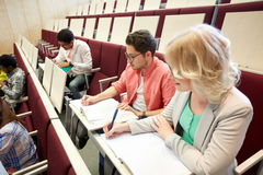Group of students with notebooks at lecture hall royalty free stock image