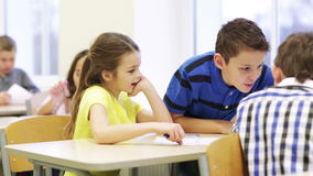 Group of students with papers talking at school. Education, elementary school, learning and people concept - group of school kids with pen and papers talking in stock footage