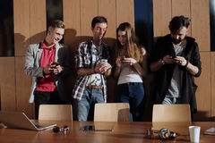Group of students with the phones in their hands standing in the room near the wooden wall. Friends showing something to stock photo