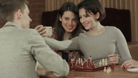 Group of students playing chess, while taking selfie photo stock video footage