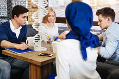 Group of students preparing project work in genetics. Work in group of four. Cheerful diligent international students sitting at the table and working on the royalty free stock photography