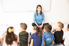 Group of students in a preschool classroom. Preschool teacher and a group of students sitting on the floor and learning something new at school stock image