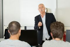 Group students with professor in modern school classroom. Group of students with professor in modern school classroom Royalty Free Stock Images
