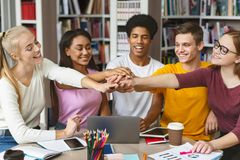 Group of students putting their hands up together in library royalty free stock photo