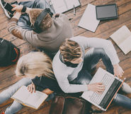 Group of students reading books,  and studyin on the floor Royalty Free Stock Photos