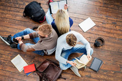 Group of students reading books, writing in notebooks. And using a smartphone leaning on each other on wooden floor Stock Photography
