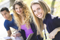 Group of students sitting on a bench. A group of three students sitting on a bench outdoors, focus on the foreground Royalty Free Stock Image