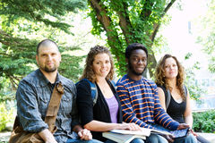 Group of students sitting on bench. Group of University students sitting on bench outside royalty free stock photo