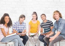 Group of students sitting in front of brick grey background. Digital composite of Group of students sitting in front of brick grey background Stock Photo