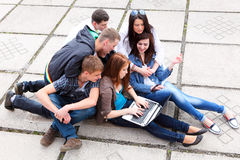 Group students sitting with a laptop on stree Royalty Free Stock Photos
