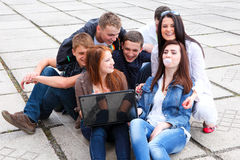 Group students sitting with a laptop on stree Royalty Free Stock Photography