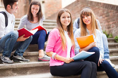 Group of students sitting outdoors Stock Photos