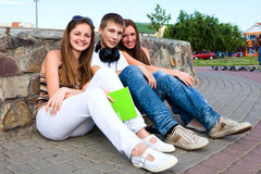 Group of students sitting on street Stock Image