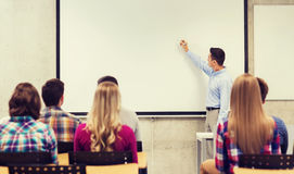 Group of students and smiling teacher in classroom. Education, high school, teamwork and people concept - smiling teacher standing in front of students and Stock Photo