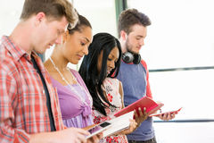 Group of students standing with books. Group of students standing in row with books in their hands Stock Photo