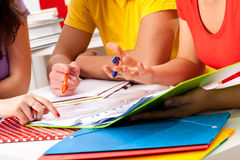 Group of students studying from notes. Group of students studying together from notes on a desk Stock Images