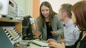 A group of students studying at the university as an engineer. Sit around the booth with the equipment. Several people stock footage