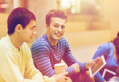 Group of students with tablet pc and coffee cup royalty free stock photography