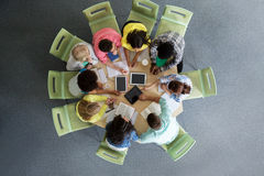 Group of students with tablet pc at school library. Education, high school, people and technology concept - group of international students sitting at table with royalty free stock photo