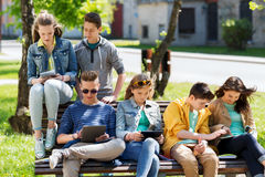 Group of students with tablet pc at school yard. Education, high school and people concept - group of happy teenage students with with tablet pc computers at Stock Image