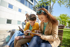 Group of students with tablet pc at school yard. Education, high school and people concept - group of happy teenage students with tablet pc computers at campus Royalty Free Stock Image
