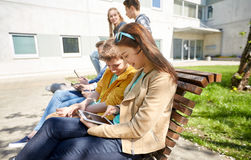 Group of students with tablet pc at school yard. Education, high school and people concept - group of happy teenage students with tablet pc computers at campus Royalty Free Stock Photo